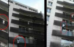 man saves a child who is hanging on balcony