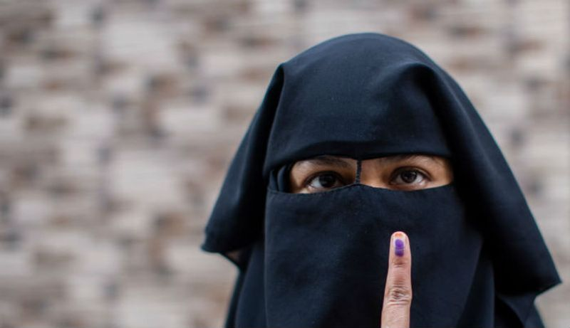 An Indian Muslim woman shows her indelible ink marked finger after casting her vote outside a polling station in Shaheen Bagh on February 8, 2020 in Delhi.