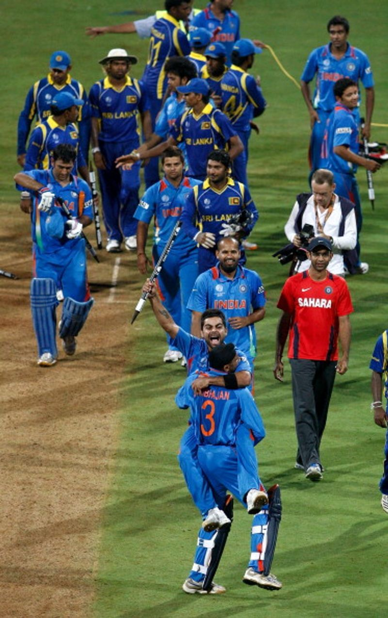 Indian players run on to the pitch and celebrate.