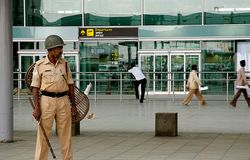 policeman keeps watch in front of the Bangalore International Airport in Bangalore, India, on Wednesday, May 21, 2008. Bangalore International Airport Ltd., partly owned by Unique Zurich and Siemens AG, said it will start operations a day later than planned at the instruction of India's Ministry of Civil Aviation.
